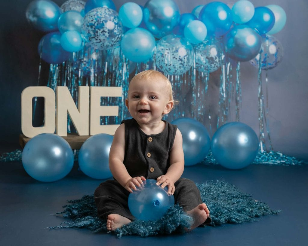 Baby boy in portrait on Blue balloon backdrop. Taken during 1st birthday celebrations and cakesmash photoshoot in Glasgow