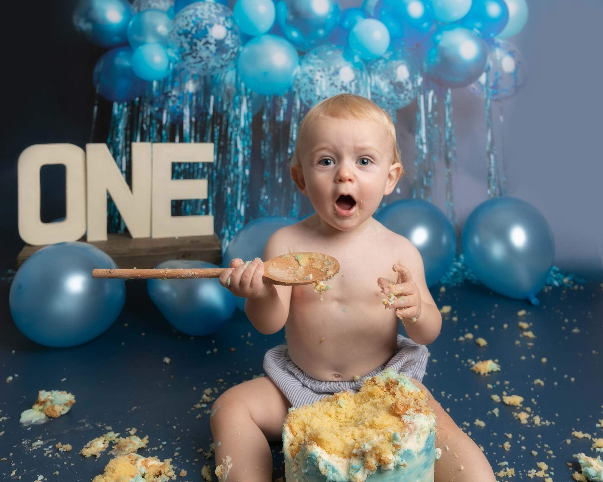 Baby boy sat with a 1st birthday cake and holding a wooden spoon. Boy sits on a blue backdrop with balloons at Glasgow studio during his cakesmash photoshoot