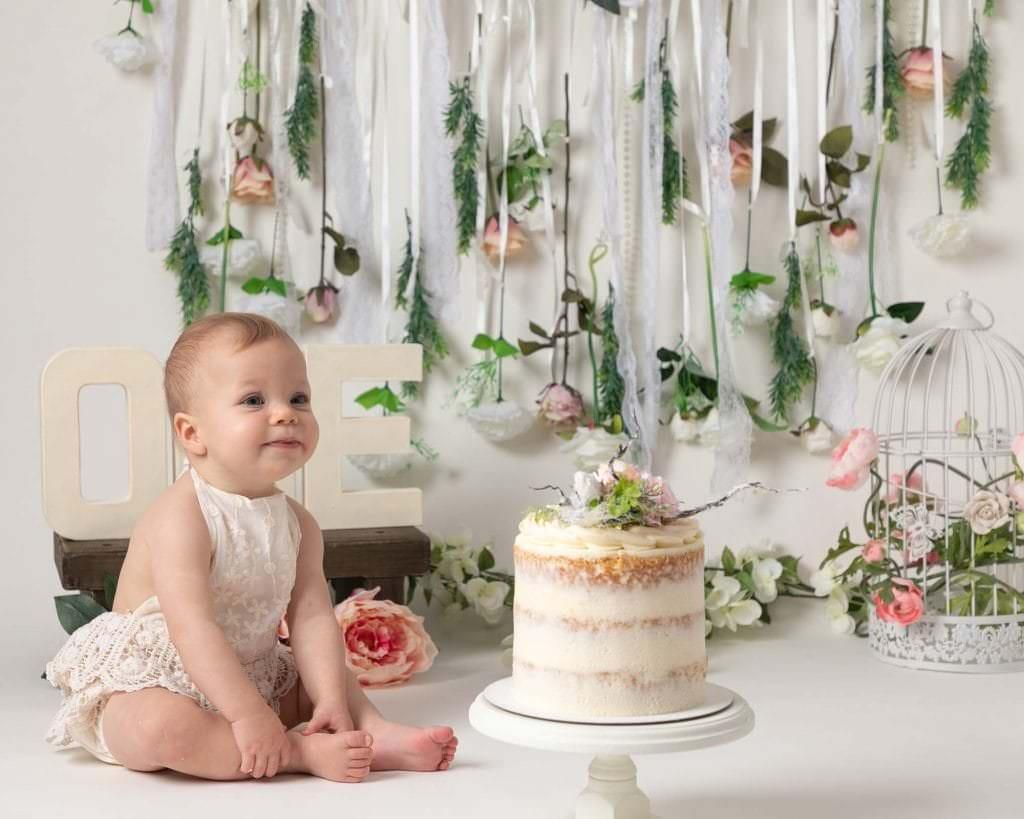 Baby girl in cream romper at 1st birthday photoshoot in Glasgow