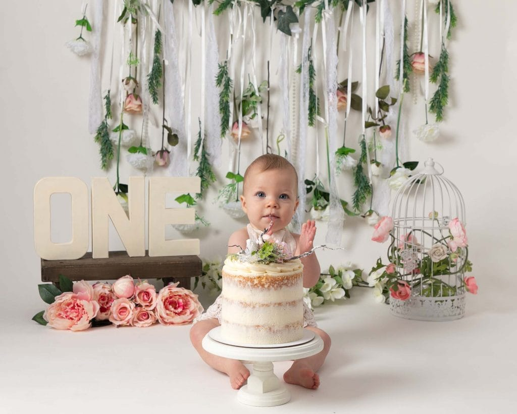 Baby girl sat in front of pink floral backdrop, with birthday cake. Baby is taking part i her 1st birthday cakesmash photoshoot in Glasgow