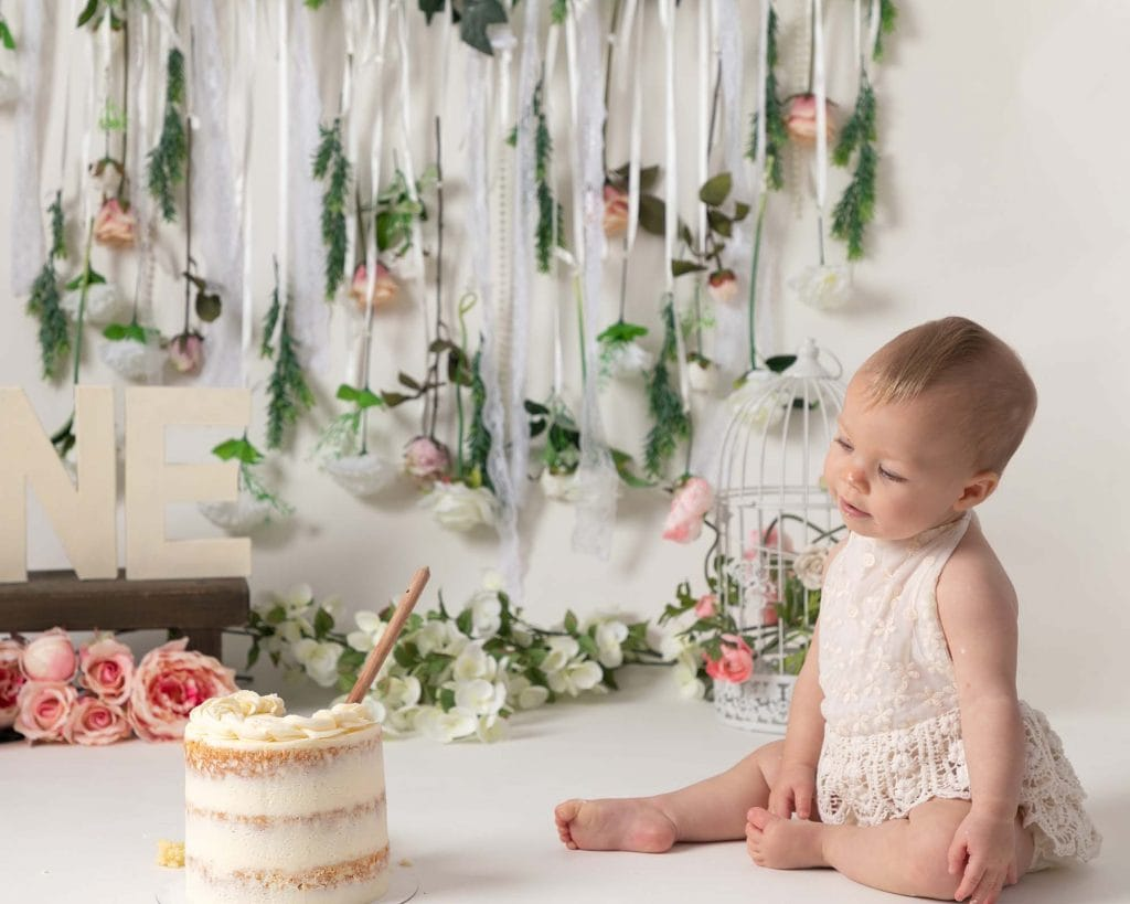 Little girl sat on boho backdrop with flower garland, looking at her 1st birthday cake, during cakesmash photoshoot at Glasgow studio