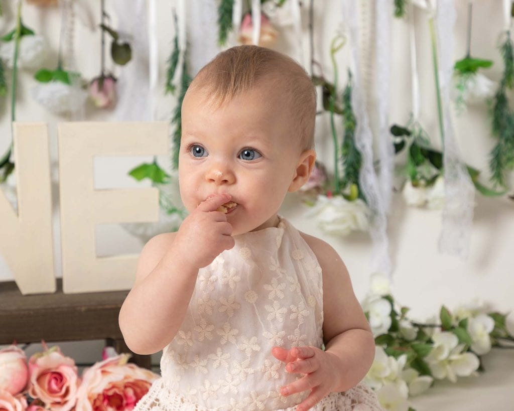 Baby girl eating 1st birthday cake in Glasgow at her photoshoot