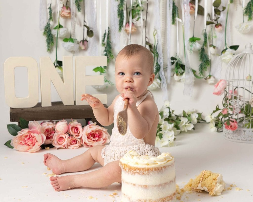 Baby girl with wooden spoon and cake at 1st birthday photoshoot in Glasgow