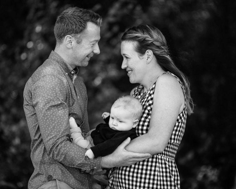 Black & White image offparents holding baby, facing each other and smiling at one and other.
