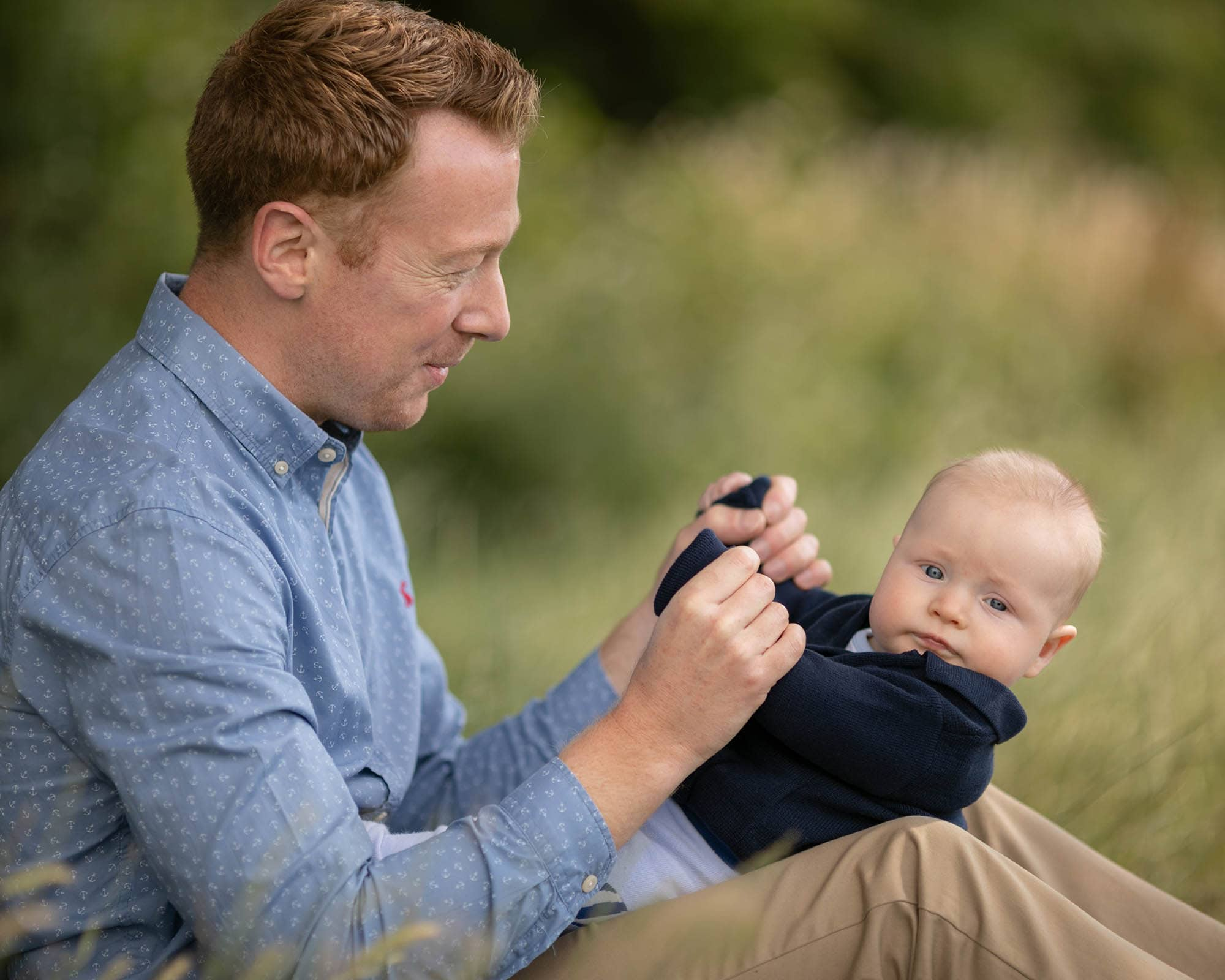 Dad in blue shirt holding baby on his lap. Profile shot. Image taken in Glasgow park at family photography session