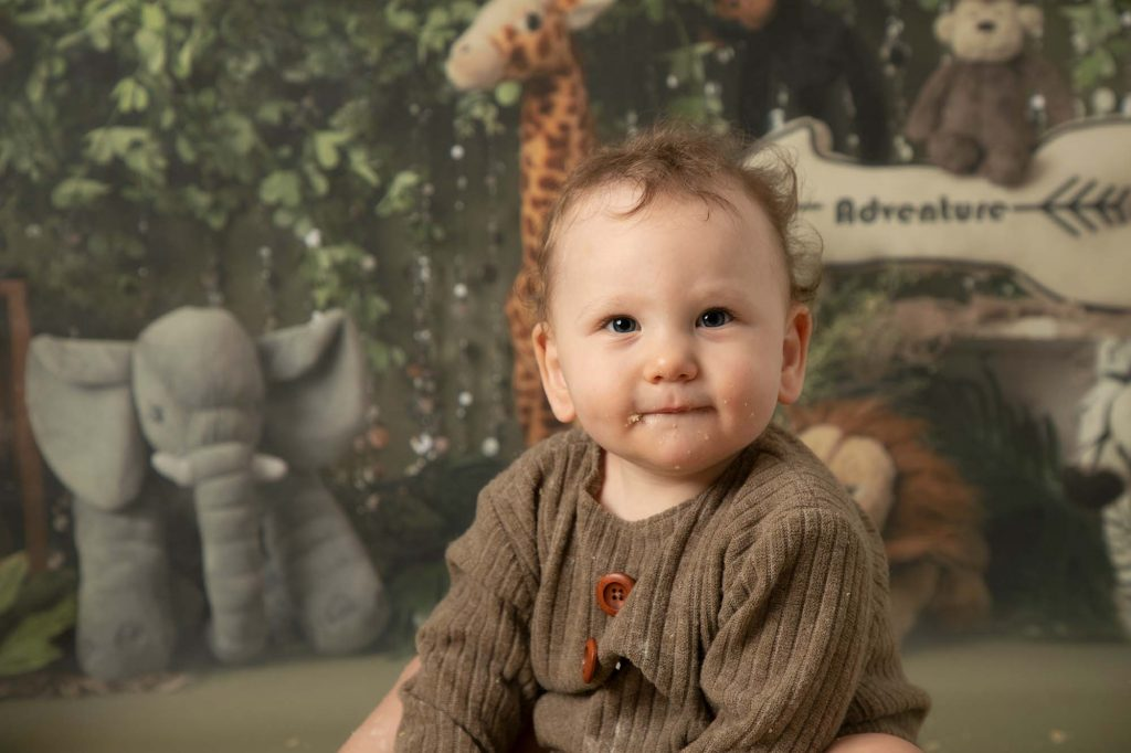 Baby boy in brown romper sat on a jungle backdrop as part of 1st birthday cakesmash photoshoot in Glasgow