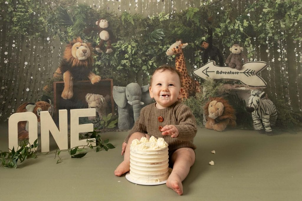 Baby boy sat with cream 1st birthday cake, in front of a jungle scene backdrop, smiling at the camera. Image part of a cakesmash photoshoot taken by Glasgow photographer