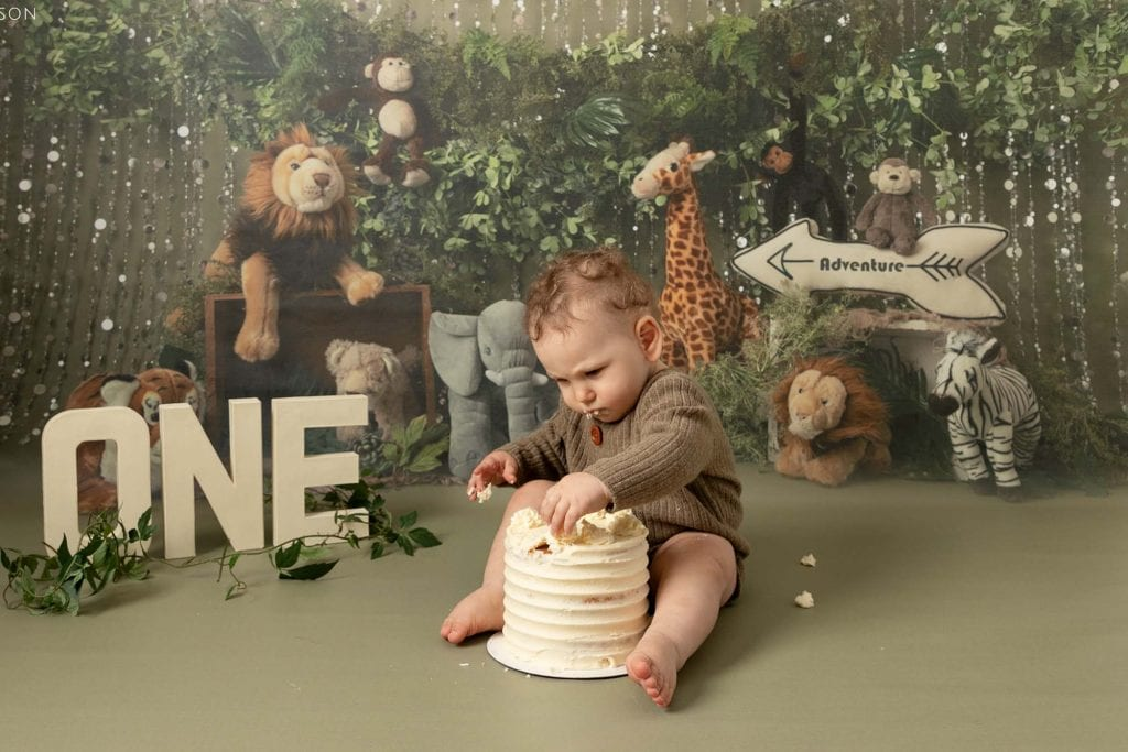 Baby boy sat on green jungle backdrop, with a birthday cake between his legs. Celebrating his 1st Birthday at Glasgow studio with a cakesmash photoshoot