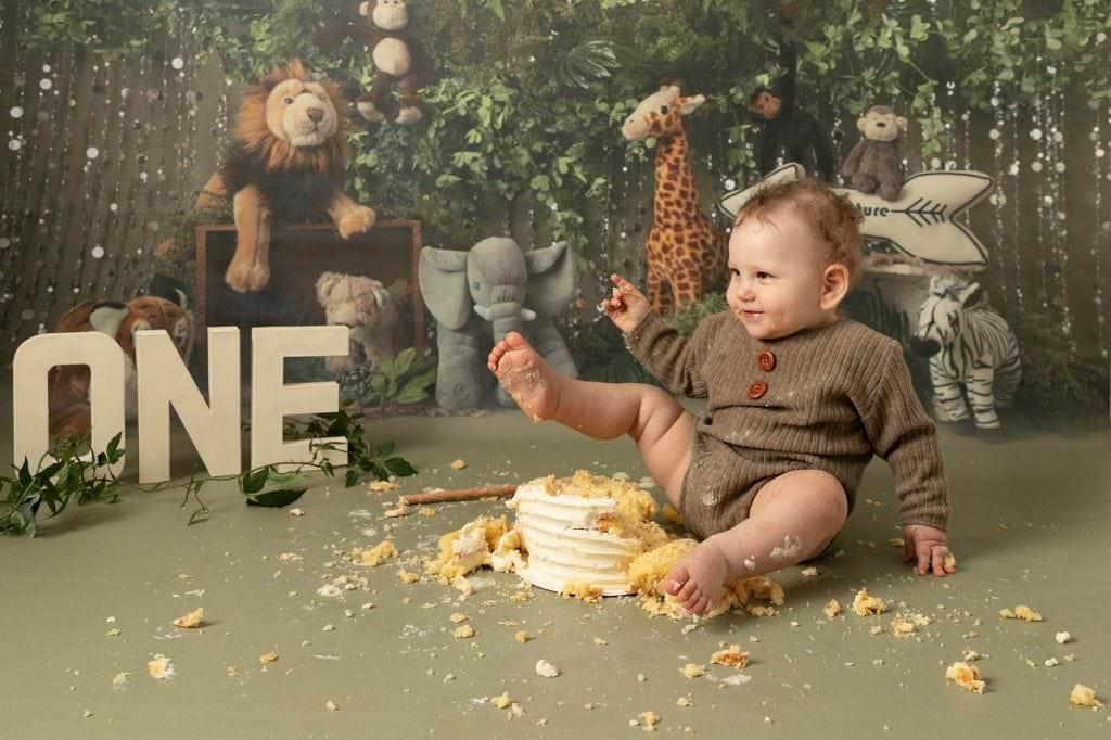 Baby boy in brown romper sat on jungle backdrop, kicking his 1st birthday cake. image taken at cakesmash photoshoot in Glasgow