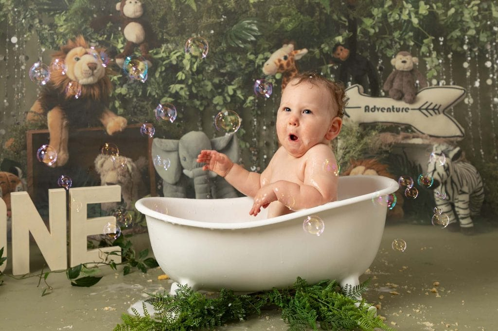 Baby boy on his 1st Birthday during cakesmash photoshoot, sat in bath pulling a funny face. Image taken at Glasgow Studio